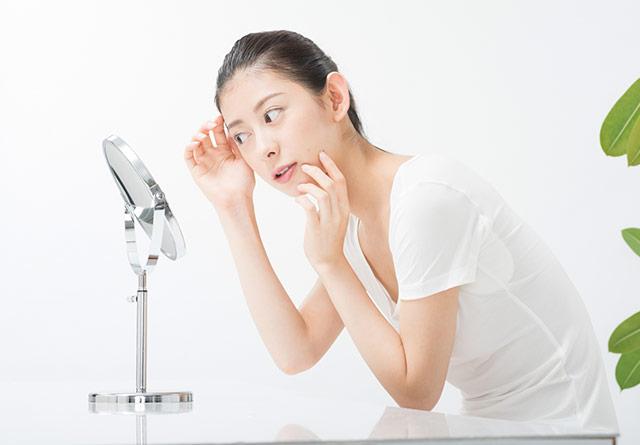 鏡の前でお肌を気にする女性
